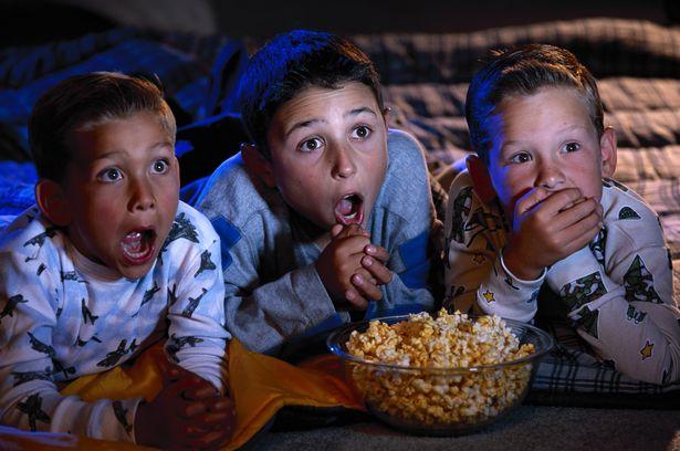 Three boys eating popcorn