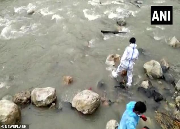 Local workers in PPE attend to the crisis on the banks of the river Bhagirathi in the town of Uttarkashi in Uttrakhand