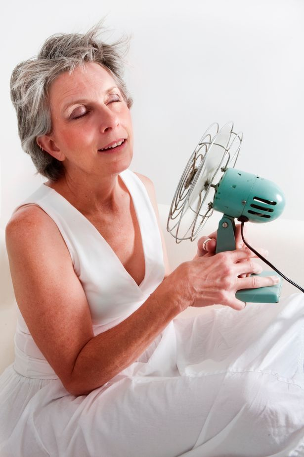 A woman using a fan to cool off