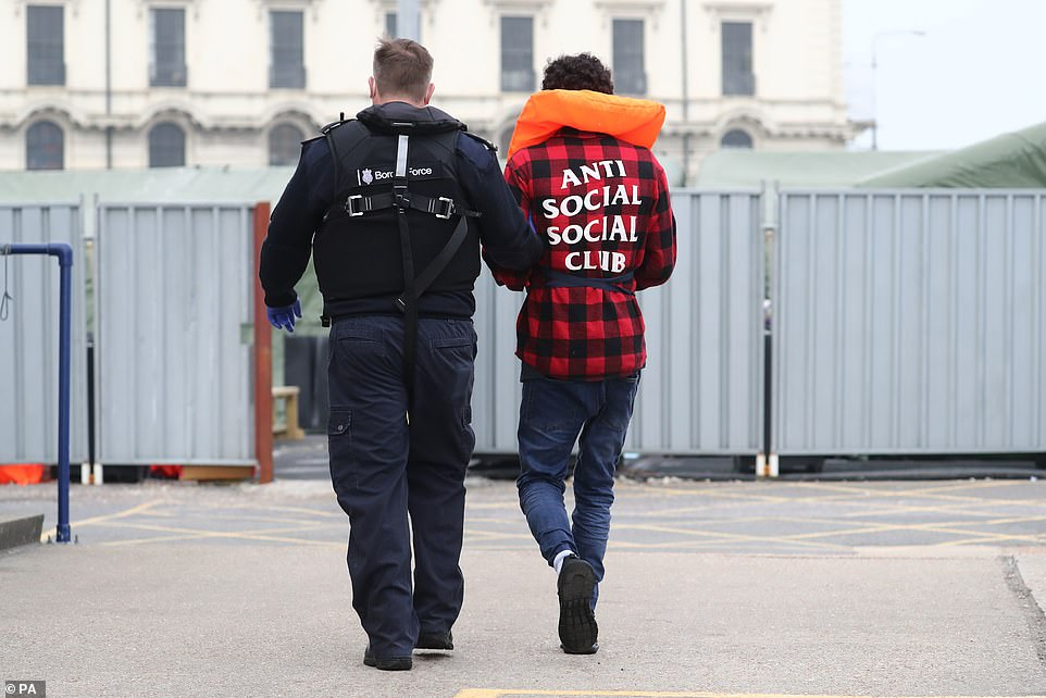 A Border Force worker accompanies a migrant after he arrives at Dover Marina in Kent today following a small boat incident