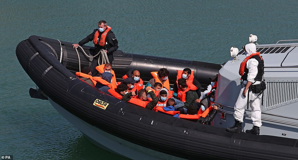 A group of migrants are brought into Dover Marina in Kent this morning after crossing the Channel in a small boat
