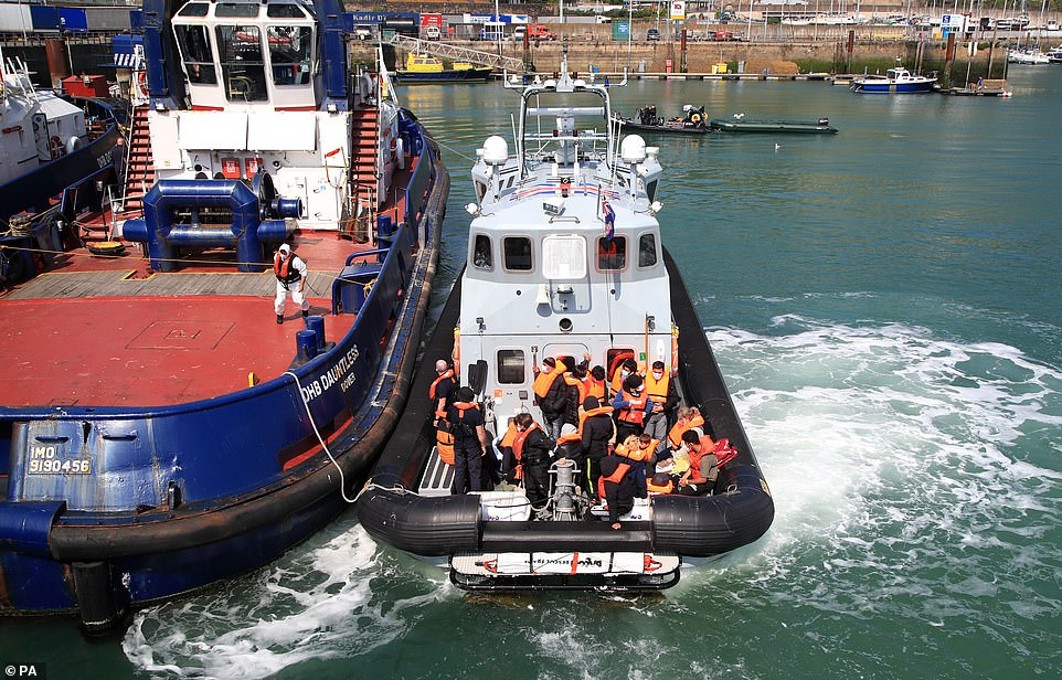 A group of migrants are brought into Dover Marina in Kent today following a small boat incident in the Channel this morning