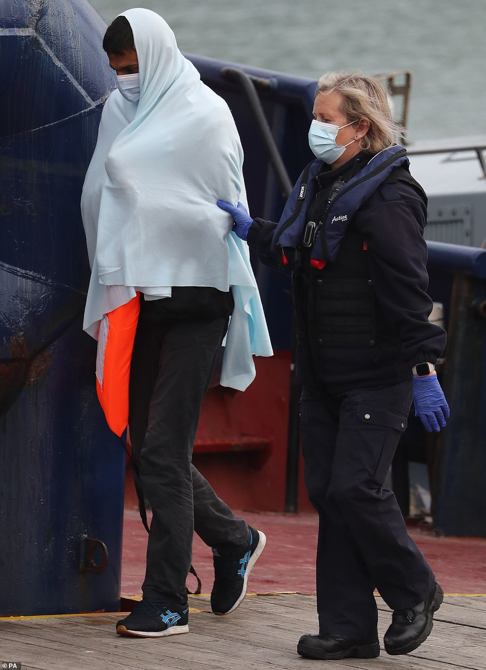 A migrant is escorted onto Dover Marina by a Border Force official this morning following a small boat incident in the Channel
