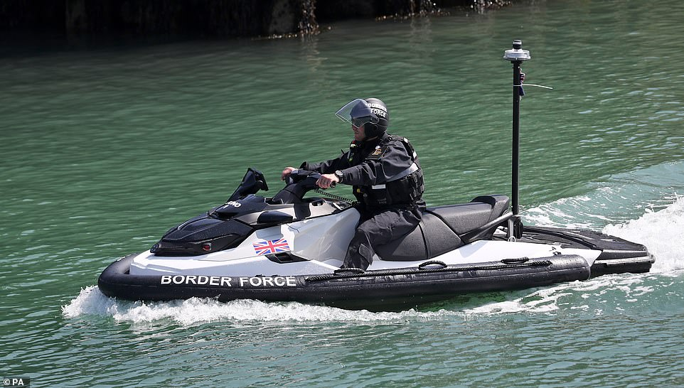 A Border Force officer arrives on a jet ski into Dover Marina in Kent today as small boats continue to cross the Channel