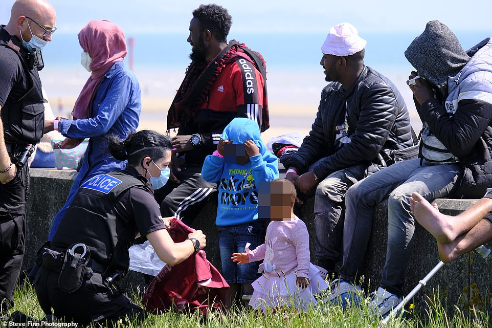 Police officers attend to two youngsters after a group of migrants landed on the beach at Dymchurch in Kent today