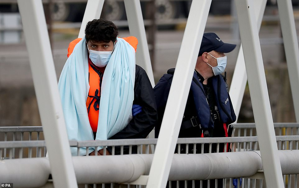 A migrant wears a face mask as he is accompanied to shore at Dover Marina in Kent by a Border Force official this morning