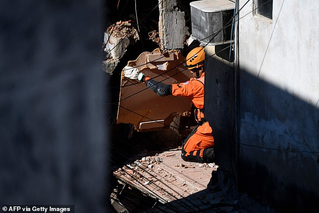 A rescue worker looks for victims of an early morning building collapse at the Rio das Pedras favela in Rio de Janeiro
