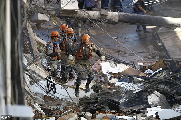 Firefighters continue to search for survivors after pulling a woman alive from the debris on Thursday