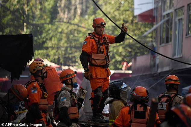 Firefighters pull a woman from the debris after an early morning building collapse in Rio das Pedras