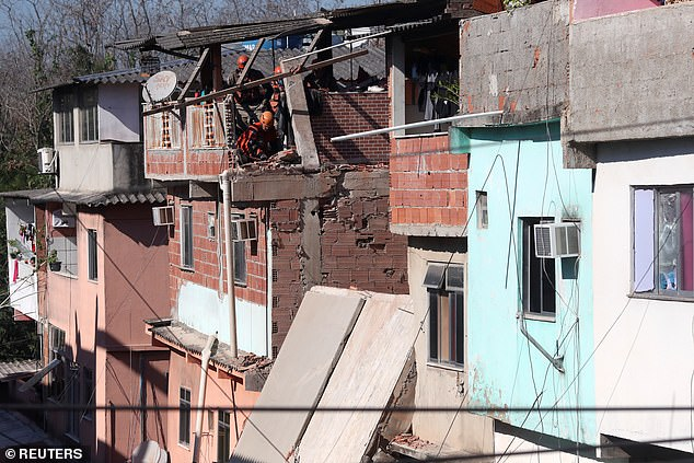 The construction in Rio das Pedras damaged nearby residences as it collapsed (pictured, firefighters check over damage caused to other houses)