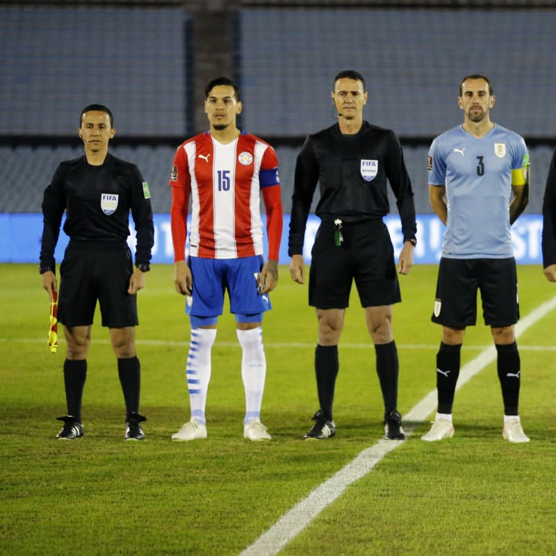 Referee Wilmar Roldán (3L) poses with captains Gustavo Gómez of Paraguay (2L) and Diego Godín of Uruguay (4L)