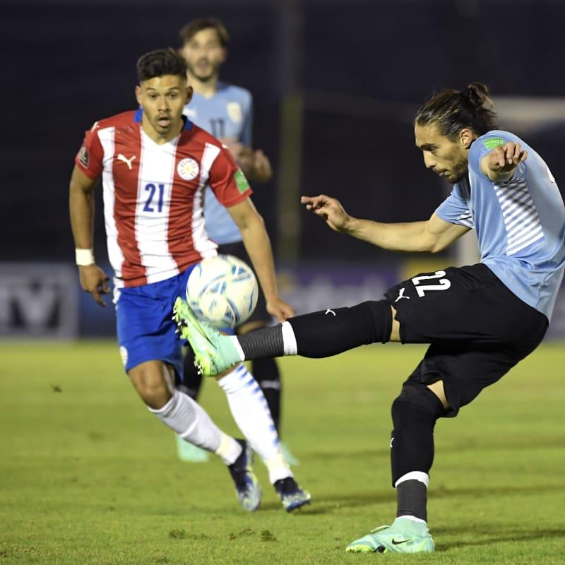 Martín Cáceres of Uruguay kicks the ball against Óscar Romero of Paragua