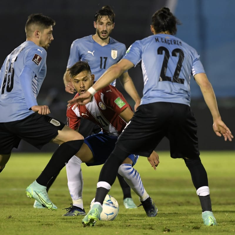 Óscar Romero of Paraguay fights for the ball with Federico Valverde (L) and Martín Cáeres (R)
