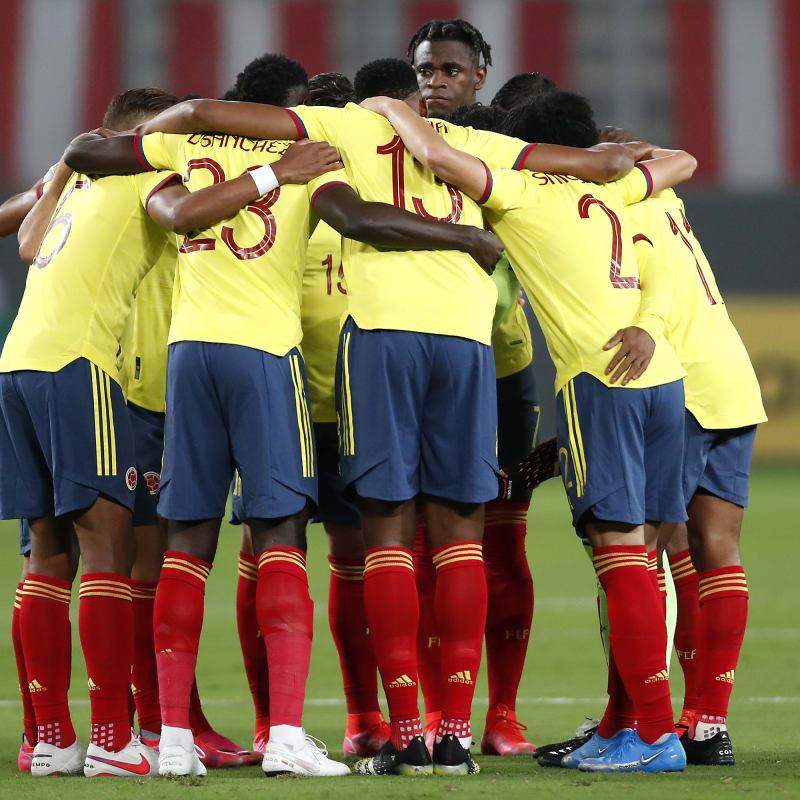 Players of Colombia huddle before a match between Peru and Colombia