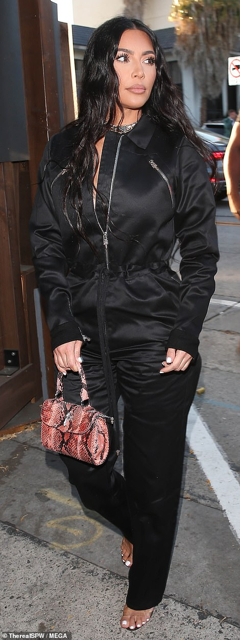 Edgy: Giving the modest ensemble a bit of edge, Kim layered a slew of chunky silver chains around her neck and toted her belongings in a small snakeskin handbag