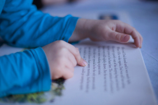 Close up boys fingers pointing to words in book.