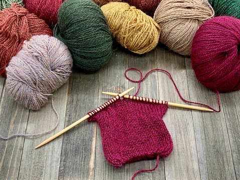 High Angle View Of Multi Colored Balls Of Yarn And Knitting On Wood