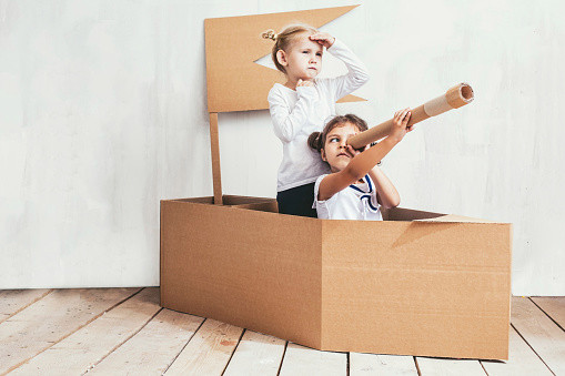 Two children little girls home in a cardboard ship play captains and sailors