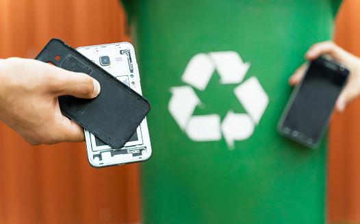 A broken smartphone being put into a green recycling bin.