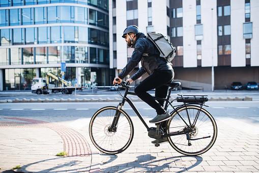 A young man riding a bike through a city.