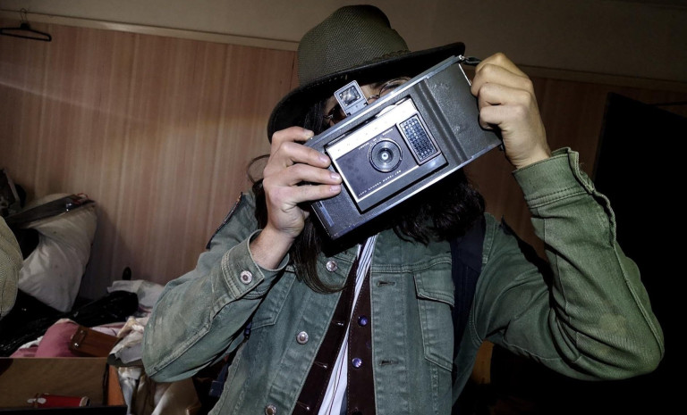 Joshua poses with a retro polaroid camera that was discovered during the exploration.