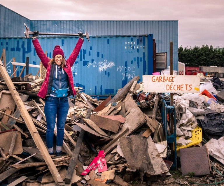 Sol Escobar standing on a pile of broken wood in a camp in Calais. She is wearing a red hat and jacket and holding a metal pole above her head