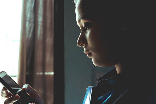 girl holding book and texting on mobile phone