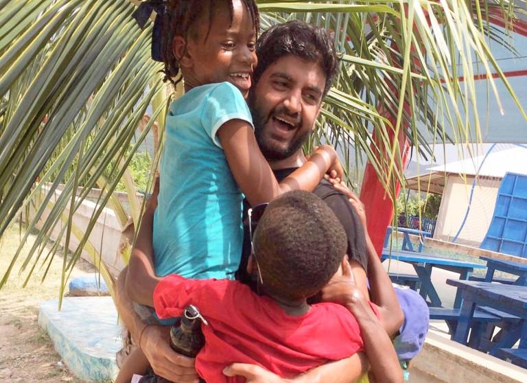 Krishan Parmar cuddling some kids in Haiti