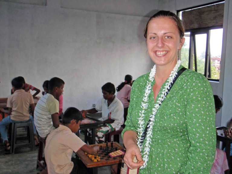 Libby Brewster in Sri Lanka. She is wearing a green dress and is standing in front of some children sitting down