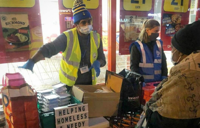 Kirshan Parman at a supermarket giving out food donations. He is wearing a high vis vest, face mask and a hat. In front of him is a sign that says 'helping homeless and needy'