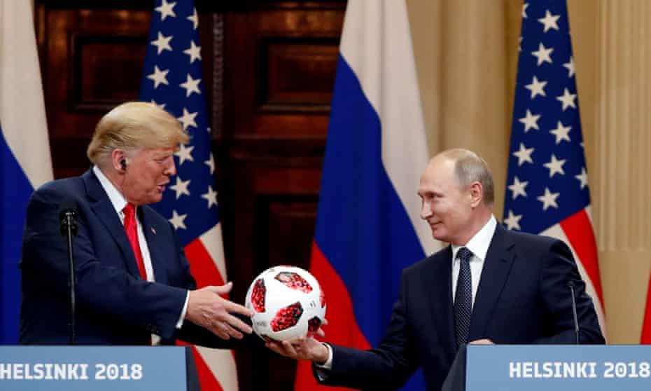 Donald Trump receives a football from Vladimir Putin in Helsinki in 2018.