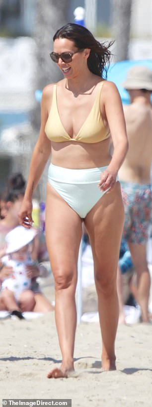 Mixing it up: Kristen, 38, was seen in a mismatched bikini, featuring a plunging gold top and high waist aqua blue briefs