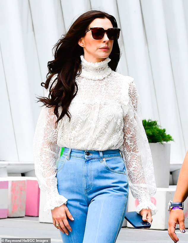 Transformed: Hathaway also wore a long raven wig and shielded her eyes with large sunglasses as she strutted on to the set with her iPhone in her hand