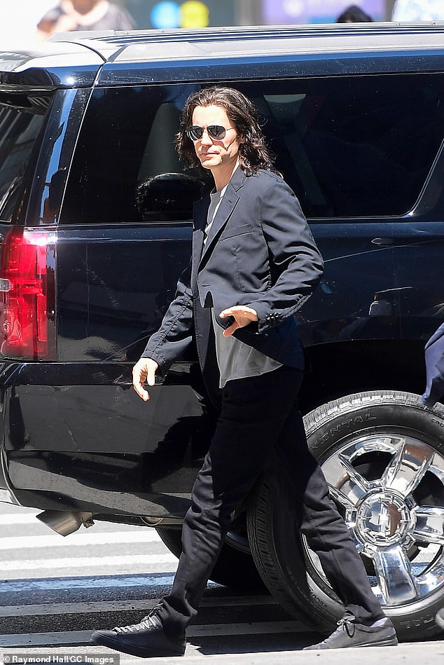 Friendly wave:Jared reported to set while wearing a black suit over a light grey T-shirt and dark grey sneakers