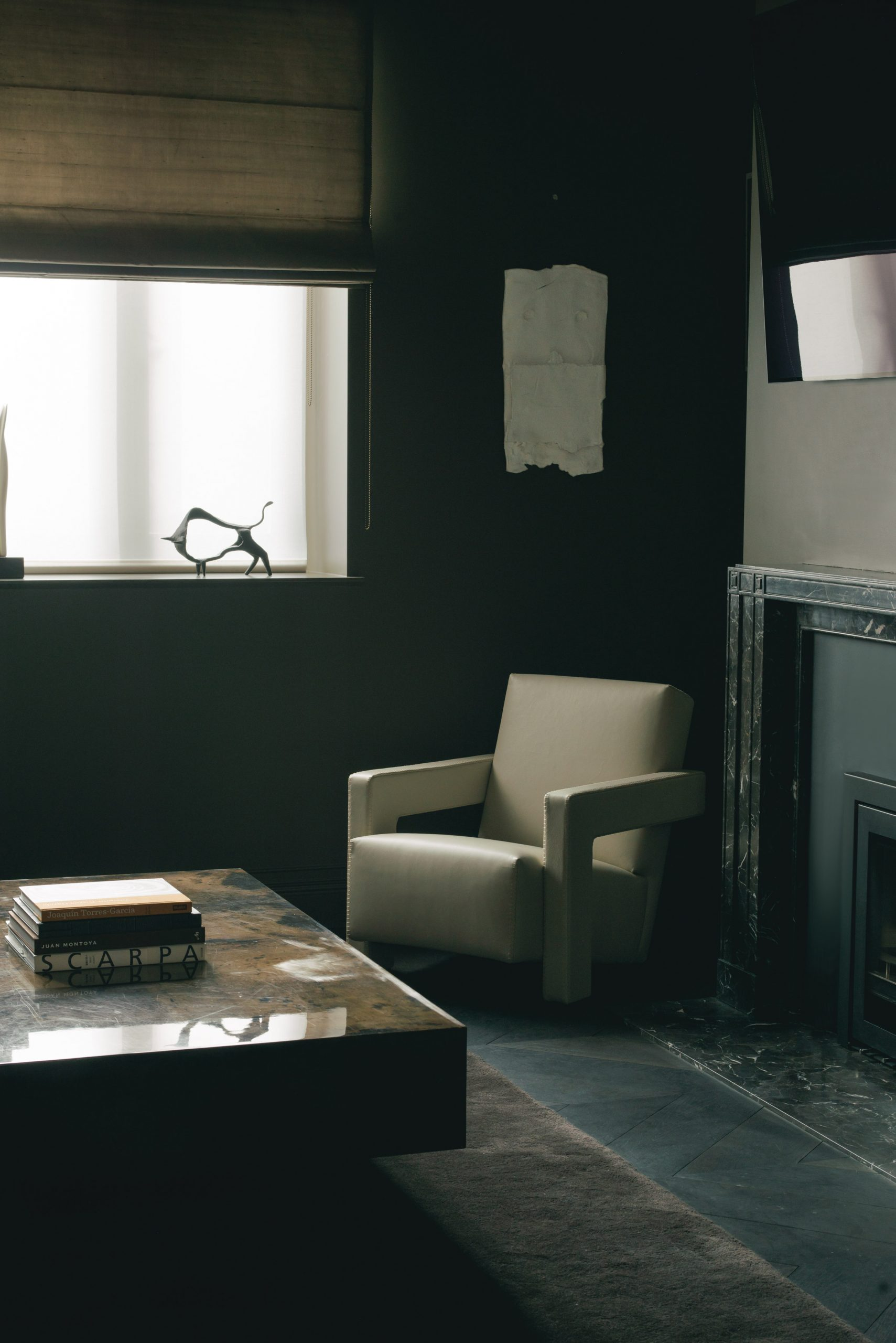 White armchair in dark room with stone coffee table and fireplace in London office by Hollie Bowden