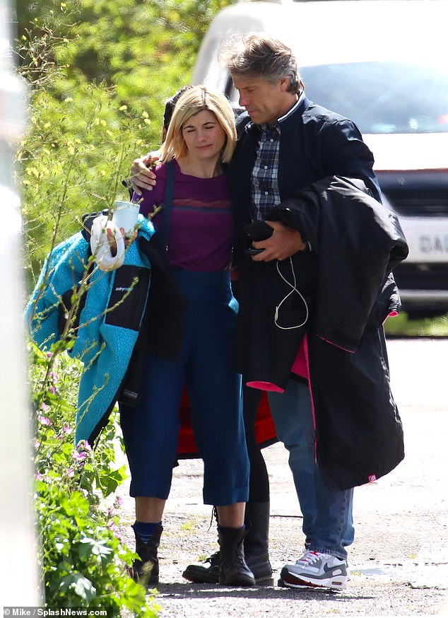 In character:Jodie was seen in costume as the iconic Time Lord as she donned a purple shirt with colourful stripes and tucked it into a pair of blue dungaree trousers