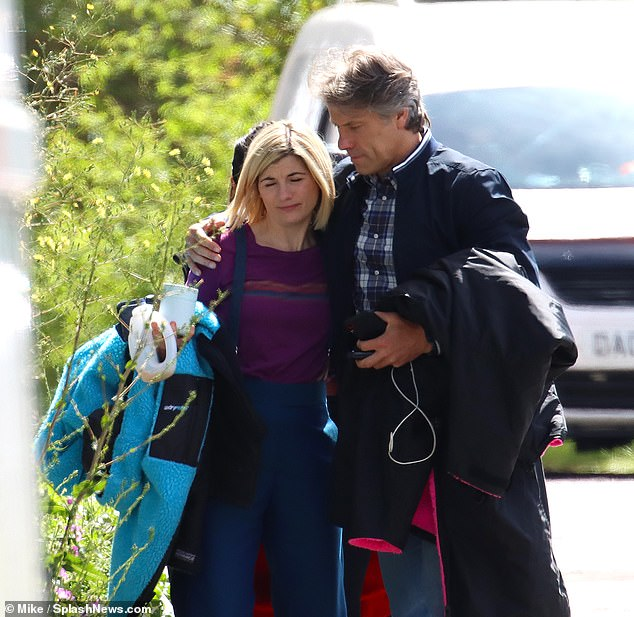 Comfort: Jodie and John were seen talking to each other before she wrapped an arm around his waist and he draped his over her shoulders for a brief embrace.