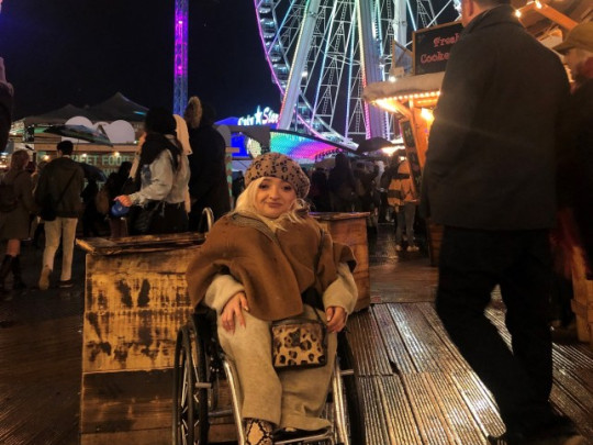 Sam Renke pictured in her wheelchair amongst crowded street food stalls at night