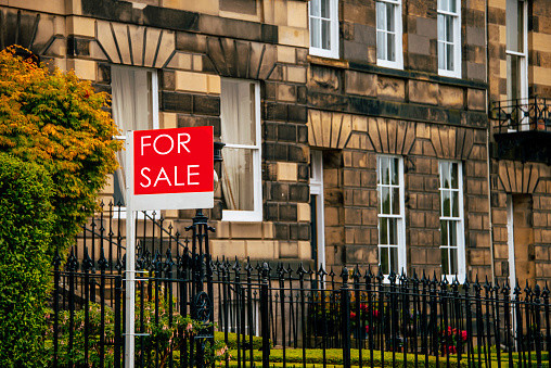 An estate agents board outside a house