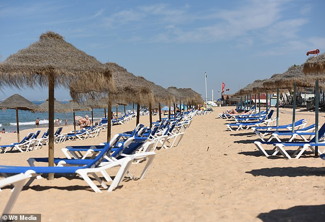 Mostly-empty sunloungers are seen on a beach in the Algarve after British visitors fled, taking hopes of a lucrative summer season with them