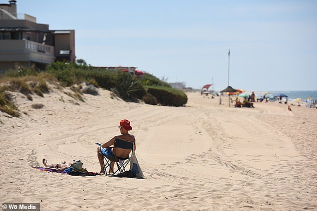 Two sunbathers enjoy a stretch of open sand in the Algarve after British tourists hurried to get home, leaving them with plenty of space