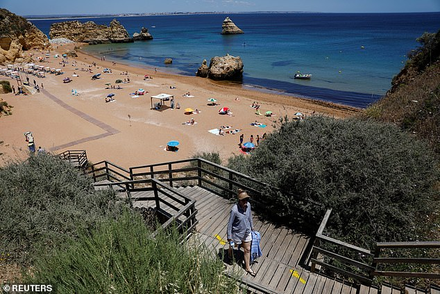 A person leaves Dona Ana beach in Lagos, Portugal, on June 3 before British visitors were ordered home - leaving tourist destinations virtually empty