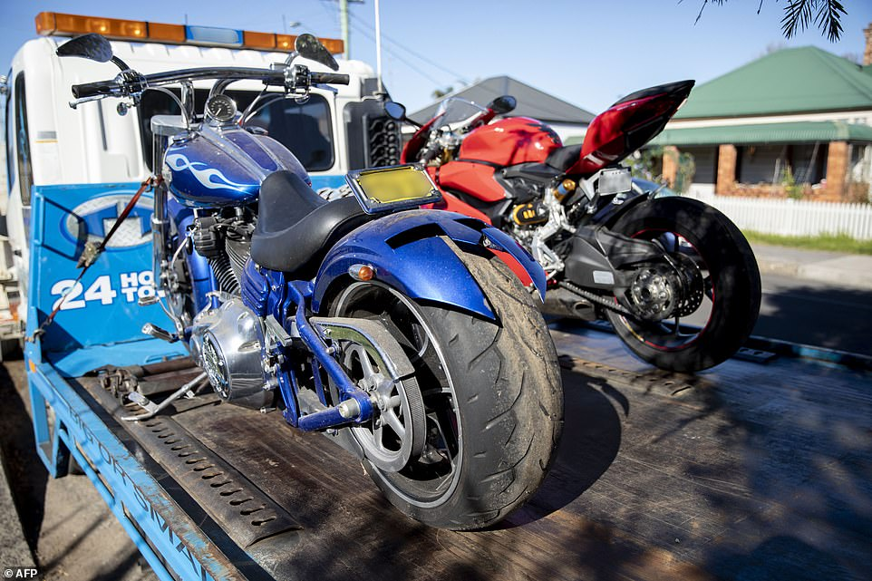 A Harley-Davidson and a Ducati (right) motorcycle are strapped to the back of a truck to be taken in by police as evidence