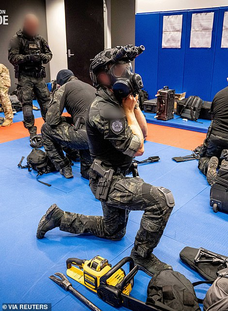Police officers in night operations gear prepare for the sting