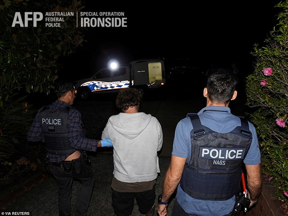 A man is led away in cuffs by police in armour vests during the huge raid which saw 200 arrested in Australia alone