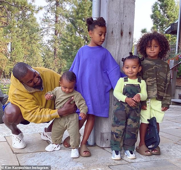 Good daddy:Another image was of the singer with all four of the kids in an outdoor setting with pine trees behind them