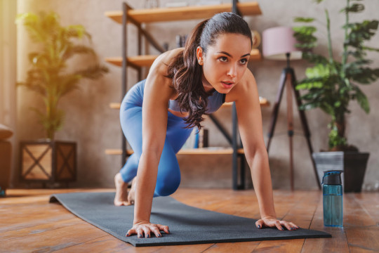 Young woman doing sport exercises indoor at home