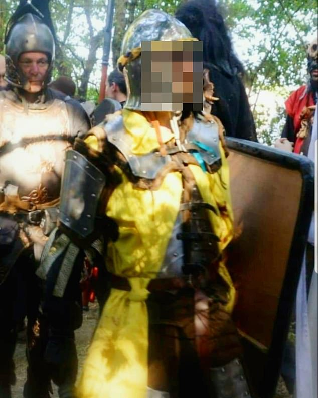 Damien T in a suit of plate armour carries a shield at a re-enactment