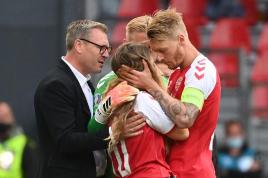 Sabrina Kvist Jensen (C), partner of Denmark's midfielder Christian Eriksen, is embraced by Denmark's defender Simon Kjaer (R) as she reacts after Eriksen collapsed during the UEFA EURO 2020 Group B football match between Denmark and Finland at the Parken Stadium in Copenhagen on June 12, 2021.