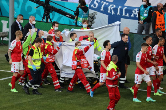 Players escort paramedics as Denmark's midfielder Christian Eriksen is evacuated from the pitch during the UEFA EURO 2020 Group B football match between Denmark and Finland at the Parken Stadium in Copenhagen on June 12, 2021.